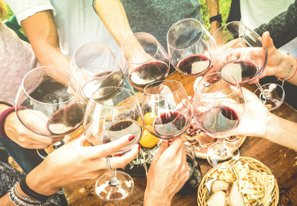 friends-hands-toasting-red-wine-glass-and-having-fun-outdoors-with-picture-id685888824