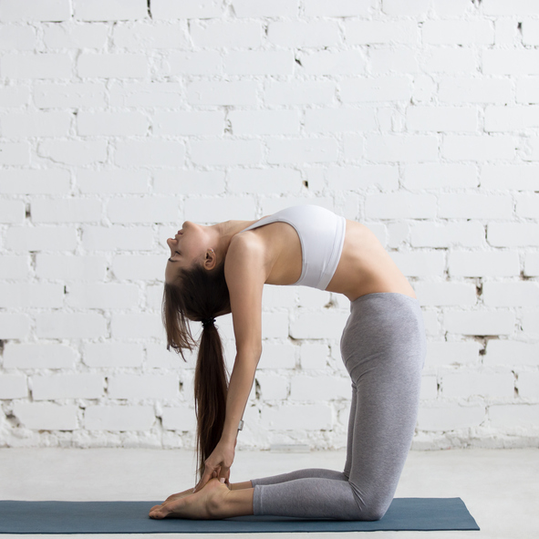 Beautiful young woman working out in loft interior, doing yoga exercise on blue mat, stretching with closed eyes, standing in Ustrasana, Camel Posture, full length, copy space